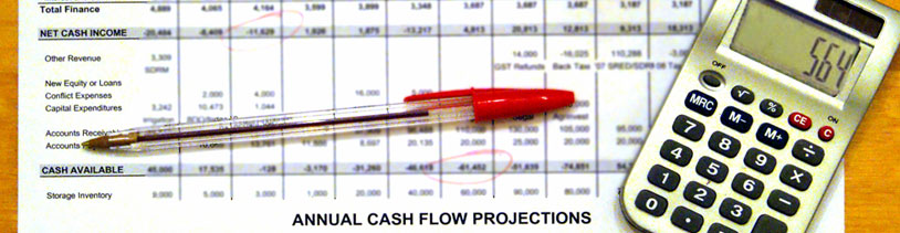 An annual cash flow spread sheet, calculator and red pen