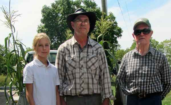 Three generations of farmers standing in front of their crop: A young girl about ten years old, a middle aged man, and a senior man.